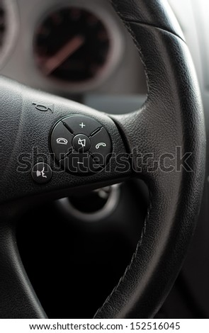 Close up of steering wheel of modern car. Volume and telephone command with cockpit background - stock photo