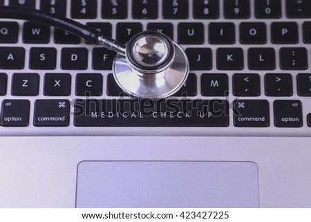 close up of stethoscope and MEDICAL CHECK UP written on laptop keyboard - stock photo