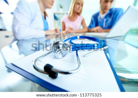 Close-up of stethoscope and paper on background of doctors and patient working with laptop - stock photo