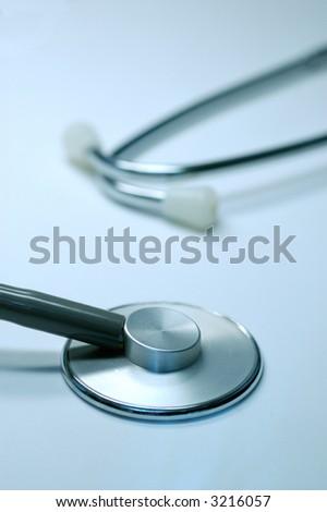 close-up of stethoscope isolated on blue background - stock photo