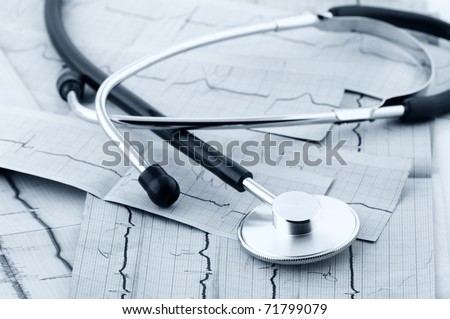 Close-up of stethoscope on cardiograms. Monochrome blue toned image. - stock photo