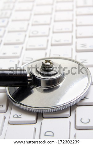 close up of stethoscope on white notebook keyboard - stock photo