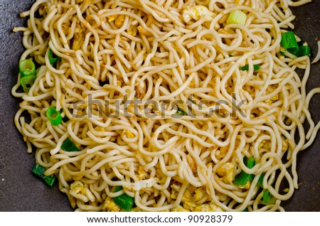 Close up of stir-fry noodles in wok pan - stock photo