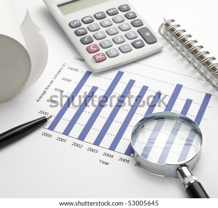 close up of stock market chart, glasses, calculator, pen and magnifying glass - stock photo