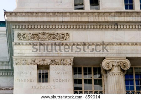 Close up of stone filigree work on a courts building downtown Denver.  At the end of the roof sits a little pigeon. - stock photo
