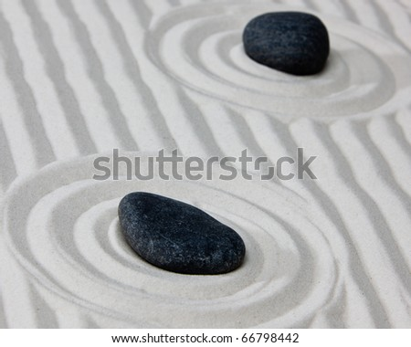 Close-up of stones on raked sand in a Japanese ornamental or zen garden. - stock photo
