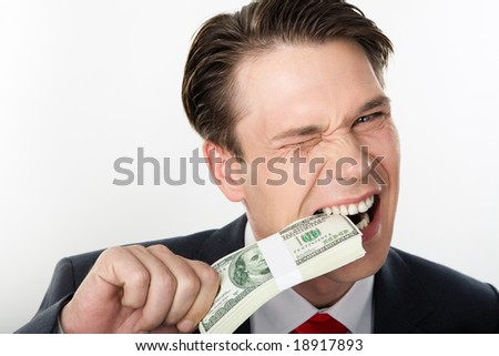 Close-up of strange businessman biting dollars by his teeth - stock photo