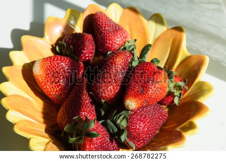 close-up of strawberries in a yellow plate