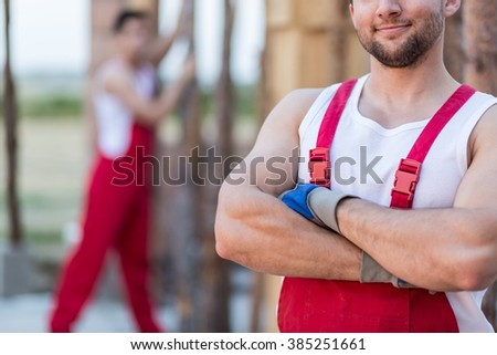 Close up of strong constructor in red work trousers - stock photo