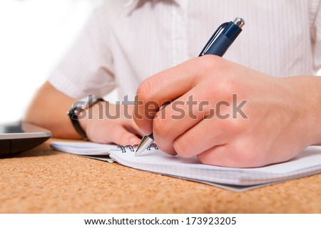 close up of student hand writing in exercise book - stock photo