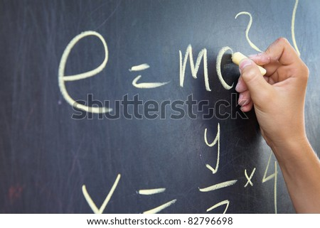 Close-up of student?s hand writing physics formula on blackboard - stock photo