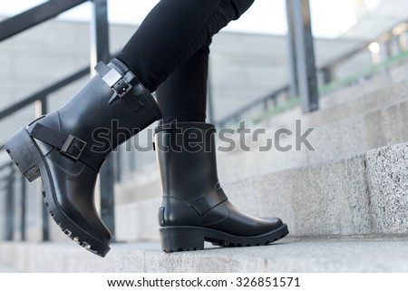 Close up of stylish female shoes boots.  Outdoor fashion shoes boots footwear concept. Fashionable stylish boots in outdoors. Urban footwear advertising - stock photo