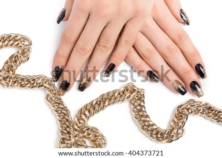 Close up of stylish hands painted black and glittery gold against a white background near shiny chain necklace - stock photo