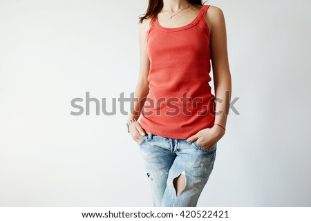 Close up of stylish red sleeveless top on female with dark hair. Cropped shot of beautiful young woman wearing trendy clothes posing against white studio wall with copy space for your advertisement - stock photo