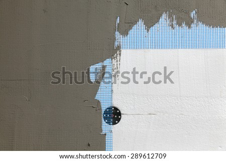 Close up of styrofoam insulation with mesh, mortar and expansion anchor on wall - stock photo
