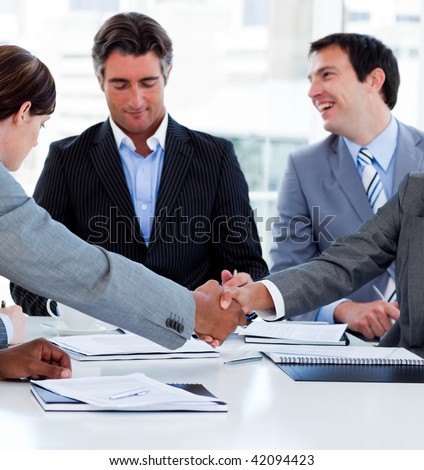 Close-up of successful business people closing a deal in a meeting - stock photo