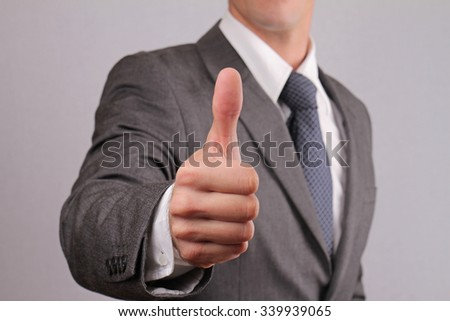 Close up of successfull businessman manager giving thumbs up. Business success concept - stock photo