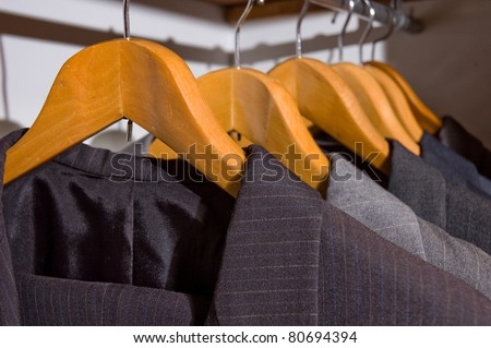 close up of suit men on wooden hangers