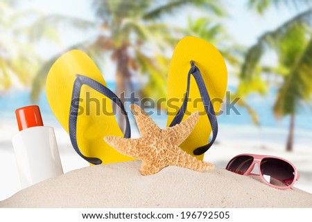 Close-up of summer accessories on sandy beach. - stock photo