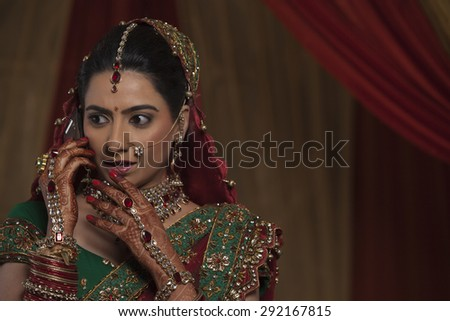 Close up of surprised young bride while talking on mobile phone