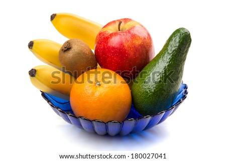 Close-up of sweet fruits in blue vase on white background - stock photo