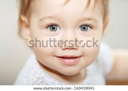 Close-up of sweet little baby face looking at camera - stock photo