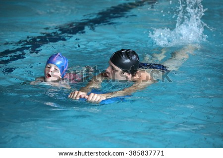 Close up of swimming lesson - child  practicing flutter kick with kick board  with instructor in  indoor swimming pool - front view - stock photo