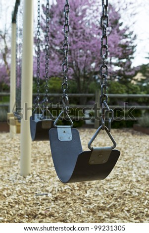 Close up of swings on empty playground with Cherry trees in background - stock photo
