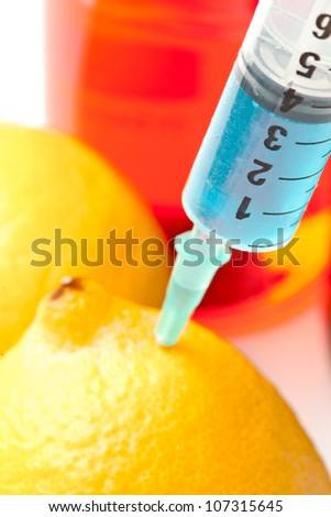 Close up of syringe into a lemon against a white background - stock photo