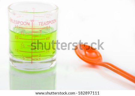 Close up of syrup measuring glass with orange spoon on glass floor. - stock photo