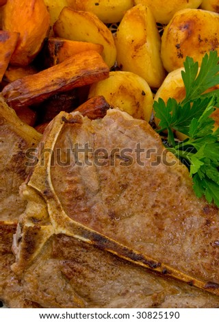 Close up of T-Bone steak with baked vegetables . - stock photo
