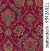 Close-up of tapestry fabric pattern with classical image of   flowers and leaves on red background. - stock photo