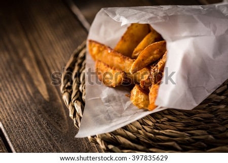 Close-up of tasty fried potato in paper on wooden table - stock photo