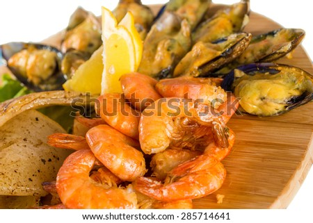 Close-up of tasty shrimps, mussels, fish with lemon on wooden board  - stock photo