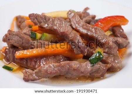 Close up of tasty veal with vegetables in the white plate