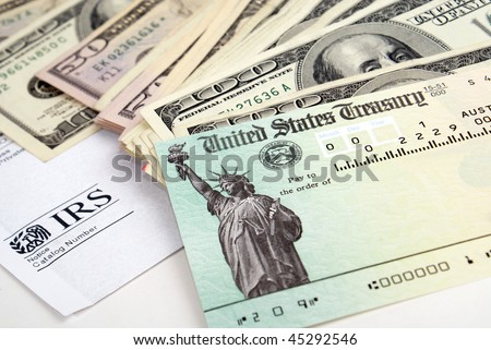 Close-up of tax return check and USA currency - stock photo
