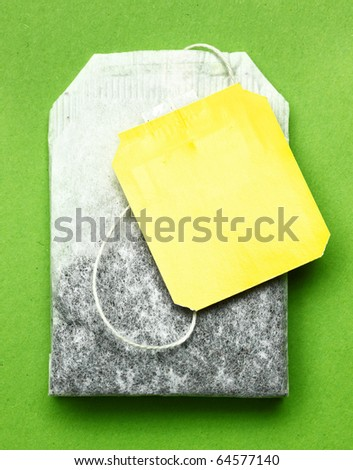 Close-up of tea bag on green placemat. - stock photo