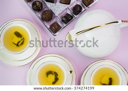 Close up of tea cups of green tea,   chocolate candies on a pink wooden background.