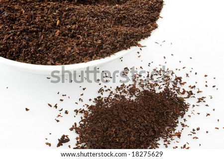 Close up of tea leaves in cup  white background
