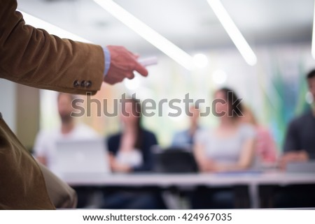 close up of teacher hand with marker while teaching lessons in school  classroom to students - stock photo