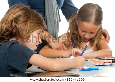 Close up of teacher supervising kids doing schoolwork. - stock photo