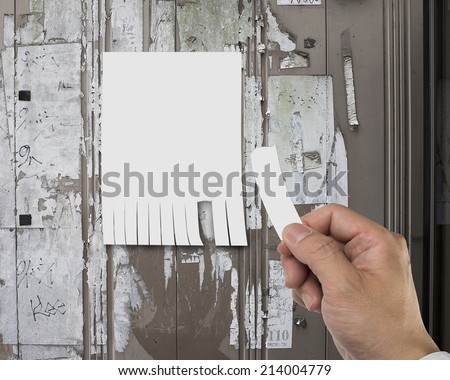 close up of tear off advertising contact information with right hand - stock photo