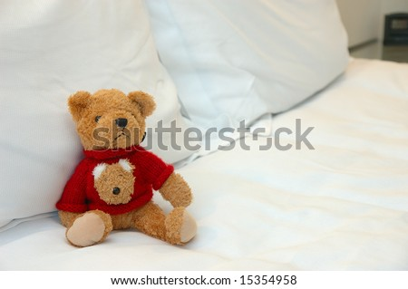Close up of teddy bear in bed
