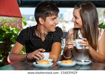 Close up of teen couple having coffee together. - stock photo