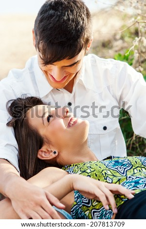Close up of Teen couple sharing intimate moment outdoors. - stock photo