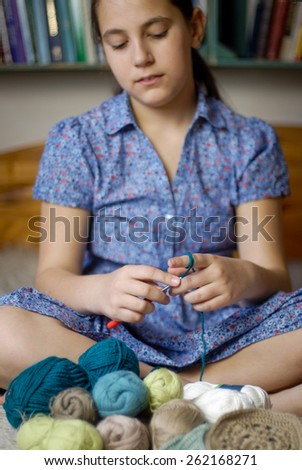 close up of teen girl with crochet hook and yarn - stock photo