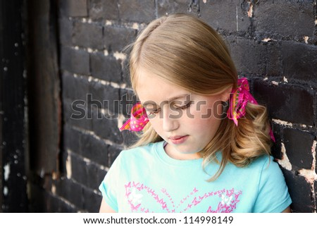 Close up of teen looking down by brick wall - stock photo