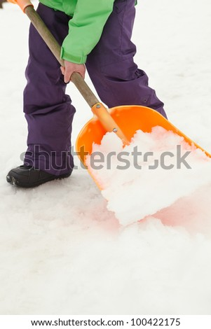 Close Up Of Teenage Boy Shovelling Snow From Path - stock photo