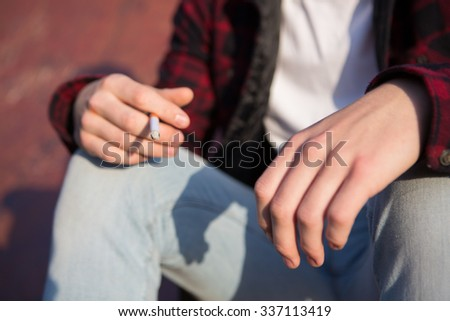 Close Up Of Teenage Boy Smoking Cigarette Outdoors - stock photo