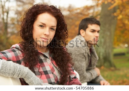 Close Up Of Teenage Couple Sitting On Bench In Autumn Park - stock photo